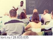 Купить «Adult African American lecturer talking students», фото № 28833035, снято 28 июня 2018 г. (c) Яков Филимонов / Фотобанк Лори