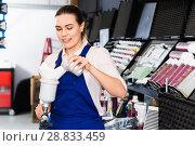 Купить «Smiling female mechanic of painting auto workshop preparing paint-spray gun», фото № 28833459, снято 4 апреля 2018 г. (c) Яков Филимонов / Фотобанк Лори