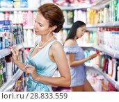 Купить «Woman customer looking for mouthwash at store», фото № 28833559, снято 21 июня 2018 г. (c) Яков Филимонов / Фотобанк Лори