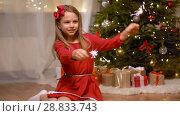 Купить «happy girl playing with sparklers at christmas», видеоролик № 28833743, снято 26 июля 2018 г. (c) Syda Productions / Фотобанк Лори