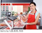 Купить «Female seller weighing sausages in shop», фото № 28835103, снято 22 июня 2018 г. (c) Яков Филимонов / Фотобанк Лори