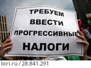 Купить «Участник митинга КПРФ на проспекте Сахарова держит плакат с требование ввести прогрессивные налоги в городе Москва, Россия», фото № 28841291, снято 28 июля 2018 г. (c) Николай Винокуров / Фотобанк Лори