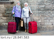 Купить «Senior ladies with travelling bags near stone wall», фото № 28841583, снято 26 ноября 2017 г. (c) Яков Филимонов / Фотобанк Лори