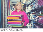 Купить «Mature female customer holding stack of linen bedsheet», фото № 28841599, снято 17 января 2018 г. (c) Яков Филимонов / Фотобанк Лори