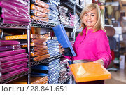 Купить «Mature female customer choosing color bedsheet in textile store», фото № 28841651, снято 17 января 2018 г. (c) Яков Филимонов / Фотобанк Лори