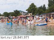Купить «Молодые люди предлагают покатать по воде детей на сказочном корабле, самолёте, лебеде на центральном пляже курортного города Евпатория, Крым», фото № 28841971, снято 29 июня 2018 г. (c) Николай Мухорин / Фотобанк Лори
