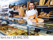 Купить «Man baker showing warm tasty bun in bakery», фото № 28842555, снято 26 января 2017 г. (c) Яков Филимонов / Фотобанк Лори