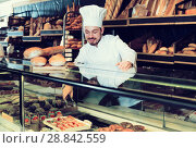 Купить «Optimistic baker showing assortment of bakery», фото № 28842559, снято 26 января 2017 г. (c) Яков Филимонов / Фотобанк Лори