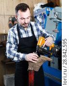 Купить «Smiling male professional worker using instruments», фото № 28842595, снято 2 февраля 2017 г. (c) Яков Филимонов / Фотобанк Лори