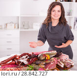 Купить «Girl shows sausages and smoked products», фото № 28842727, снято 17 августа 2018 г. (c) Яков Филимонов / Фотобанк Лори