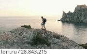 Купить «Man climbs the rocks and raises his hands», видеоролик № 28843215, снято 16 июля 2018 г. (c) Илья Шаматура / Фотобанк Лори