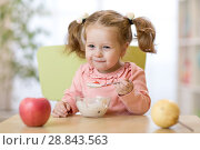 Купить «Funny child eating healthy food with a spoon at home», фото № 28843563, снято 18 августа 2019 г. (c) Оксана Кузьмина / Фотобанк Лори
