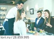 Купить «Waiter bringing dishes to guests», фото № 28859995, снято 7 ноября 2017 г. (c) Яков Филимонов / Фотобанк Лори