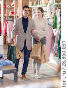 Купить «Young woman and man are walking satisfied with packadge after shopping», фото № 28860031, снято 12 марта 2018 г. (c) Яков Филимонов / Фотобанк Лори