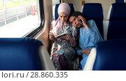 Купить «Two Muslim women traveling by train, one woman reads, another talking on the phone», видеоролик № 28860335, снято 31 марта 2020 г. (c) Константин Шишкин / Фотобанк Лори