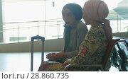 Купить «Two smiling muslim women talking to each other in the living room of airporta», видеоролик № 28860735, снято 19 сентября 2018 г. (c) Константин Шишкин / Фотобанк Лори