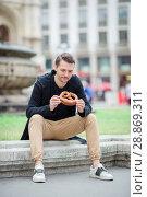 Купить «Beautiful young man holding pretzel and relaxing in park», фото № 28869311, снято 30 июня 2018 г. (c) Дмитрий Травников / Фотобанк Лори
