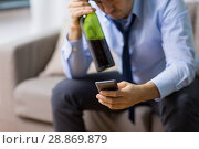 Купить «man with smartphone and bottle of alcohol at home», фото № 28869879, снято 24 ноября 2017 г. (c) Syda Productions / Фотобанк Лори