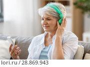 Купить «senior woman in headphones listening to music», фото № 28869943, снято 24 мая 2018 г. (c) Syda Productions / Фотобанк Лори