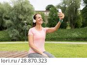 Купить «woman in phones takes selfie by smartphone at park», фото № 28870323, снято 15 июня 2018 г. (c) Syda Productions / Фотобанк Лори