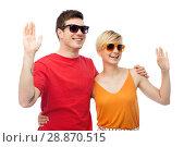 Купить «couple in sunglasses hugging and waving hands», фото № 28870515, снято 30 июня 2018 г. (c) Syda Productions / Фотобанк Лори