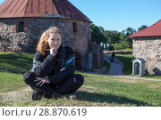 Купить «Attractive Caucasian woman wearing motorcycle outfit sitting on green meadow in some landmark attraction, copy space», фото № 28870619, снято 12 июня 2018 г. (c) Кекяляйнен Андрей / Фотобанк Лори