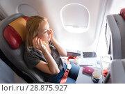 Купить «Woman flying on commercial passengers airplane, listening to music.», фото № 28875927, снято 19 октября 2019 г. (c) Matej Kastelic / Фотобанк Лори