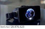 Купить «vr headset with 3d rendering of earth on screen», видеоролик № 28876623, снято 22 мая 2019 г. (c) Syda Productions / Фотобанк Лори