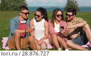 Купить «smiling friends with smartphones sitting on grass», видеоролик № 28876727, снято 19 июля 2018 г. (c) Syda Productions / Фотобанк Лори