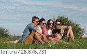 Купить «smiling friends with tablet pc sitting on grass», видеоролик № 28876731, снято 19 июля 2018 г. (c) Syda Productions / Фотобанк Лори