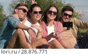 Купить «friends taking picture by selfie stick at park», видеоролик № 28876771, снято 19 июля 2018 г. (c) Syda Productions / Фотобанк Лори