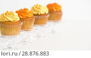 Купить «cupcakes with frosting on confectionery stands», видеоролик № 28876883, снято 13 июля 2018 г. (c) Syda Productions / Фотобанк Лори