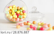Купить «close up of scattered candy drops and jar on table», видеоролик № 28876887, снято 13 июля 2018 г. (c) Syda Productions / Фотобанк Лори