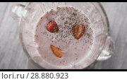 Купить «Chia seeds fall into the glass jar of the blender with red, ripe strawberries fruit and milk cream smoothies. Top view. Full HD video, 240fps,1080p. Slow motion.», видеоролик № 28880923, снято 29 июня 2018 г. (c) Ярослав Данильченко / Фотобанк Лори