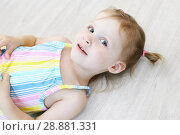 Купить «Cute little girl lying on the floor in the children's room», фото № 28881331, снято 23 июля 2018 г. (c) ivolodina / Фотобанк Лори