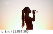 Купить «Healthy Young Sportswoman Drinking Cold Water From Plastic Bottle On Magical Sunny Evening», видеоролик № 28881583, снято 20 сентября 2018 г. (c) Константин Шишкин / Фотобанк Лори