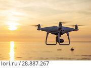 Купить «Professional drone quad copter with digital camera at sunset ready to fly for surveillance. close-up of Rotor UAV. four blade propeller drone. silhouette copter on beautiful sunset.», фото № 28887267, снято 22 июля 2018 г. (c) Алексей Ширманов / Фотобанк Лори