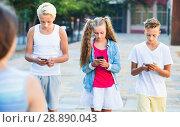 Купить «Three children keened on mobile phones during joint walk around city», фото № 28890043, снято 27 июля 2017 г. (c) Яков Филимонов / Фотобанк Лори