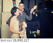 parents with daughter choosing new big TV screen in home appliance store. Стоковое фото, фотограф Яков Филимонов / Фотобанк Лори