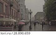 Купить «People walks on Old Arbat street during rainy summer day. Moscow downtown», видеоролик № 28890659, снято 24 июля 2018 г. (c) Ирина Мойсеева / Фотобанк Лори