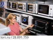 Купить «Positive female looking new microwave for kitchen in furniture store», фото № 28891759, снято 1 марта 2018 г. (c) Яков Филимонов / Фотобанк Лори