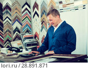 Купить «professional workman holding wooden picture framing moulding», фото № 28891871, снято 19 января 2019 г. (c) Яков Филимонов / Фотобанк Лори
