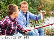 Купить «Man with teenager boy showing catch fish», фото № 28891915, снято 17 октября 2018 г. (c) Яков Филимонов / Фотобанк Лори