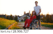 Купить «Girl On Wheelchair And Her Boyfriend Look At The Camera And Smile Slightly In The Background Of Green», видеоролик № 28906727, снято 26 сентября 2018 г. (c) Константин Шишкин / Фотобанк Лори