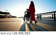 Купить «A Girl With Red Hair In Orange Dress Rolls A Disabled Guy In A Wheelchair On The Waterfront In The Sunset», видеоролик № 28906983, снято 26 сентября 2018 г. (c) Константин Шишкин / Фотобанк Лори