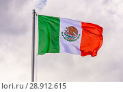 Купить «The national flag of Mexico is fluttering in the wind against a blue cloudy sky.», фото № 28912615, снято 21 июня 2018 г. (c) Акиньшин Владимир / Фотобанк Лори