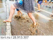 Купить «Russia, Samara, June 2018: A pedestrian crosses the road through deep water after a heavy rainfall.», фото № 28913307, снято 21 июля 2018 г. (c) Акиньшин Владимир / Фотобанк Лори