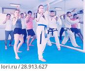 Купить «adults attempting to master new moves during karate class», фото № 28913627, снято 8 апреля 2017 г. (c) Яков Филимонов / Фотобанк Лори