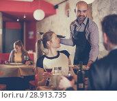 Купить «waiter bringing ordered dishes to smiling couple», фото № 28913735, снято 18 декабря 2017 г. (c) Яков Филимонов / Фотобанк Лори