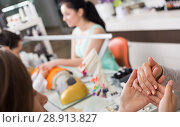 Купить «Manicurist inspecting female hands», фото № 28913827, снято 28 апреля 2017 г. (c) Яков Филимонов / Фотобанк Лори